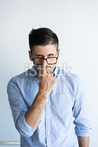 Serious guy in casual adjusting glasses. Young Caucasian man touching eyeglasses over nose. Glasses wearing concept