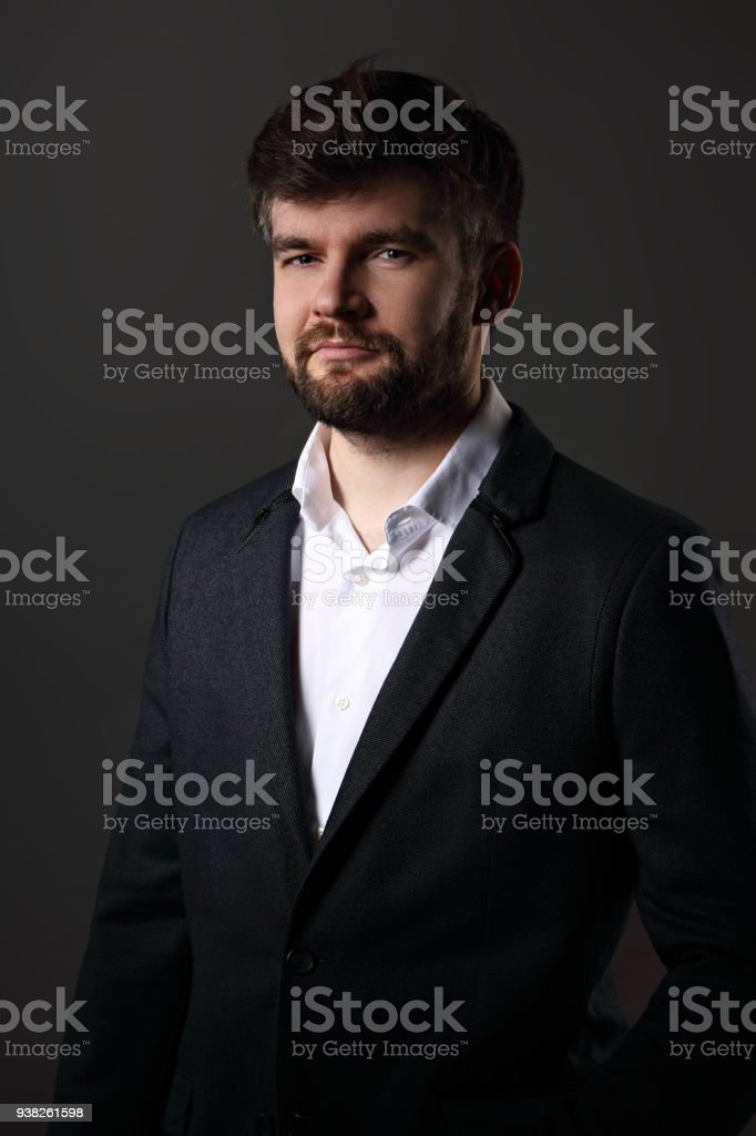 Serious handsome beard male posing in fashion suit and white style shirt looking on dark grey shadow background. Closeup portrait stock photo