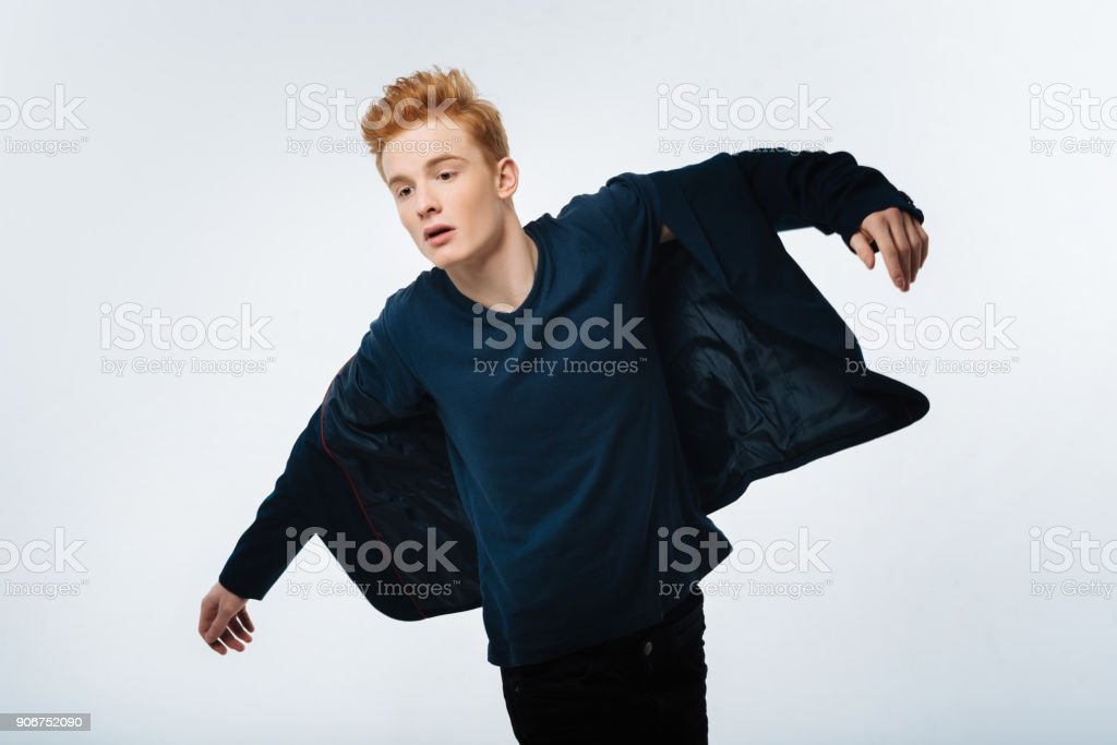 Serious handsome man putting his jacket stock photo