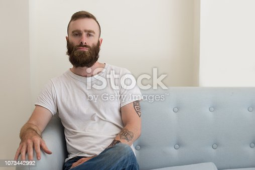 Serious handsome young bearded man with tattoo on arm sitting on sofa and looking at camera. Brutal hipster man relaxing in living room. Personality concept