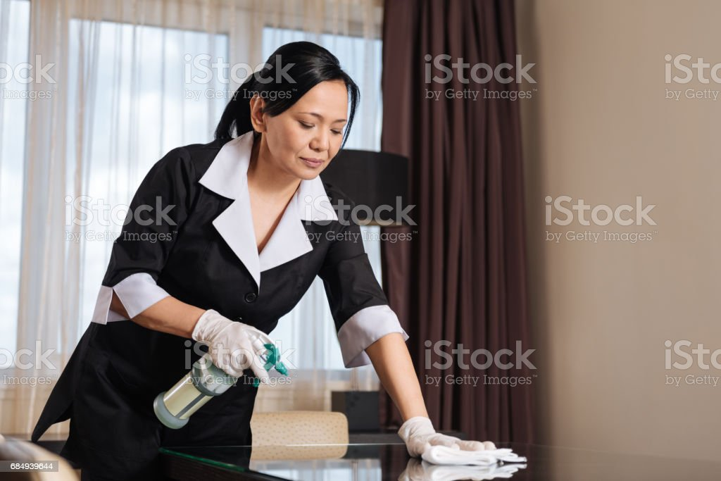 Serious hard working chambermaid making the table clean Lizenzfreies stock-foto
