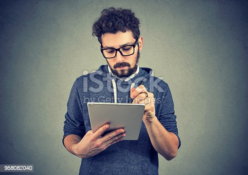 istock Serious hipster man using tablet computer 958082040
