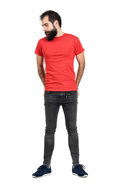 Serious hipster with hands in his back pocket looking down Serious bearded hipster in red t-shirt with hands in his back pocket looking down. Full body length portrait isolated over white studio background. men in tight jeans stock pictures, royalty-free photos & images