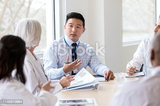 istock Serious hospital executive talks during meeting 1140610964