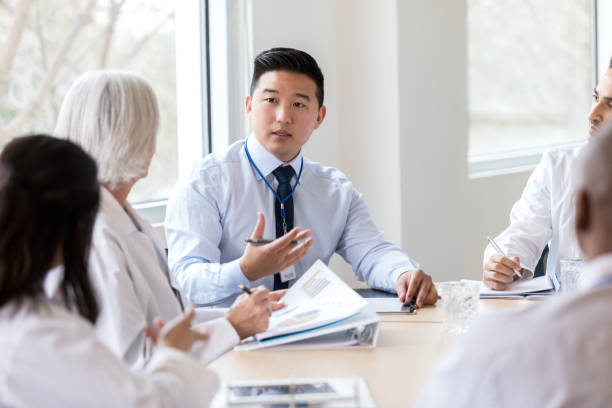 Serious hospital executive talks during meeting Male hospital administrator gestures while discussing a serious topic during a staff meeting. administrator stock pictures, royalty-free photos & images