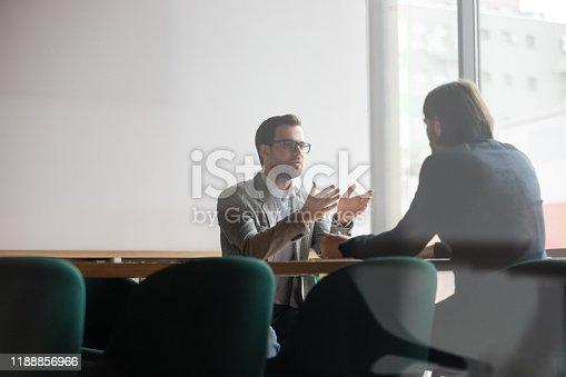 Focused confident young businessman in eyewear explaining project details to concentrated male client. Serious hr manager listening to skilled job applicant self presentation at interview in office.