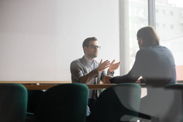 Serious hr manager listening to skilled job applicant self presentation. Focused confident young businessman in eyewear explaining project details to concentrated male client. Serious hr manager listening to skilled job applicant self presentation at interview in office. serious stock pictures, royalty-free photos & images