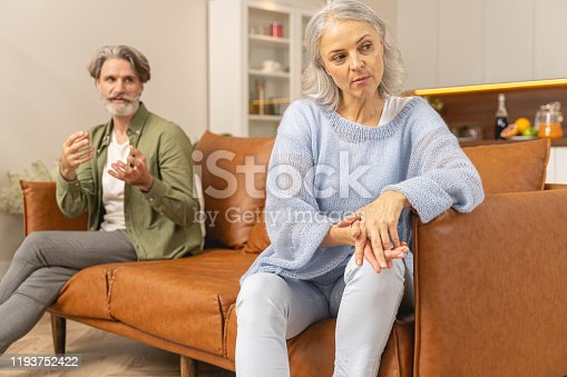 Depressed beautiful woman sitting in silence on the sofa