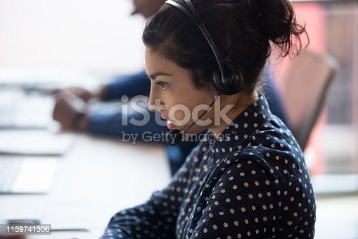 Close up of serious female indian call center agent wearing headset talk consulting client online, concentrated ethnic woman worker in earphones busy working in customer service in coworking office