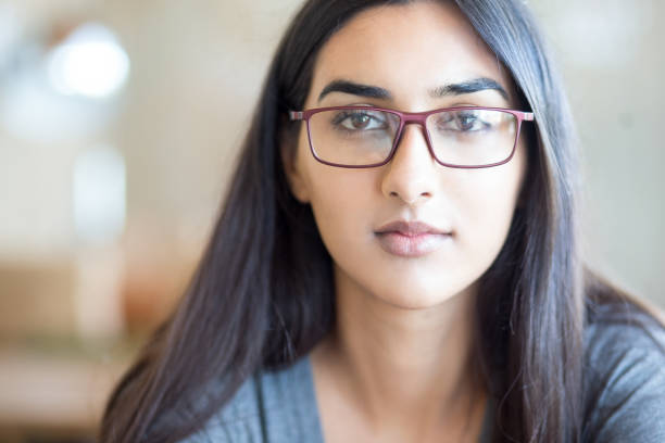 Serious intelligent female student in eyeglasses stock photo