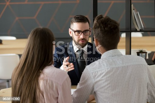 963814372istockphoto Serious investment broker, financial advisor or bank worker consulting couple 963814390