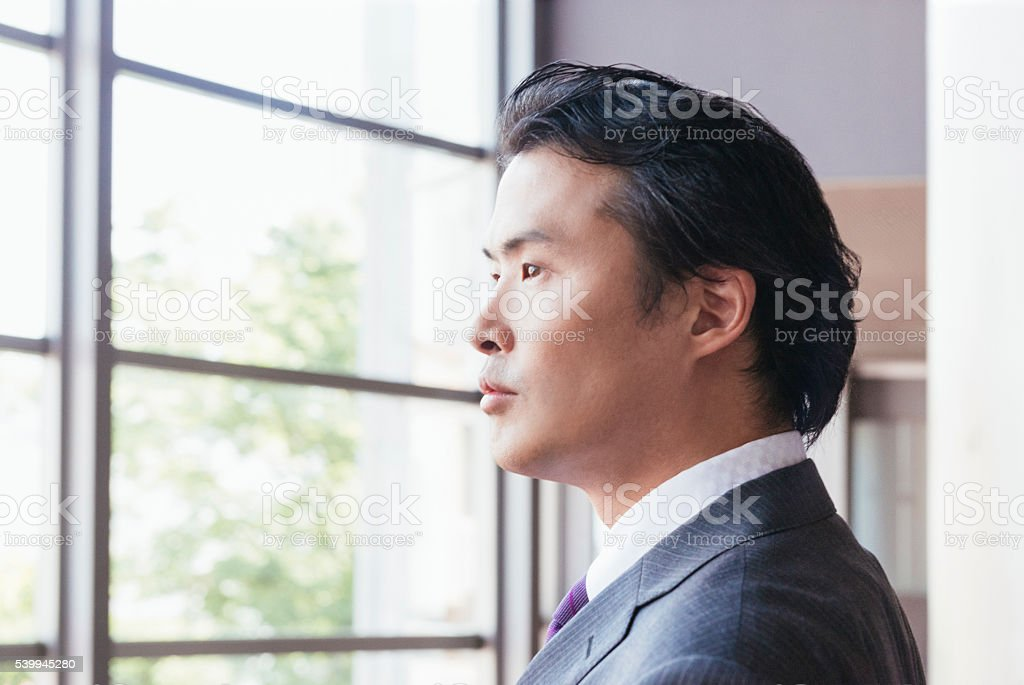 Serious Japanese Businessman Looking Out Window in Contemplation stock photo