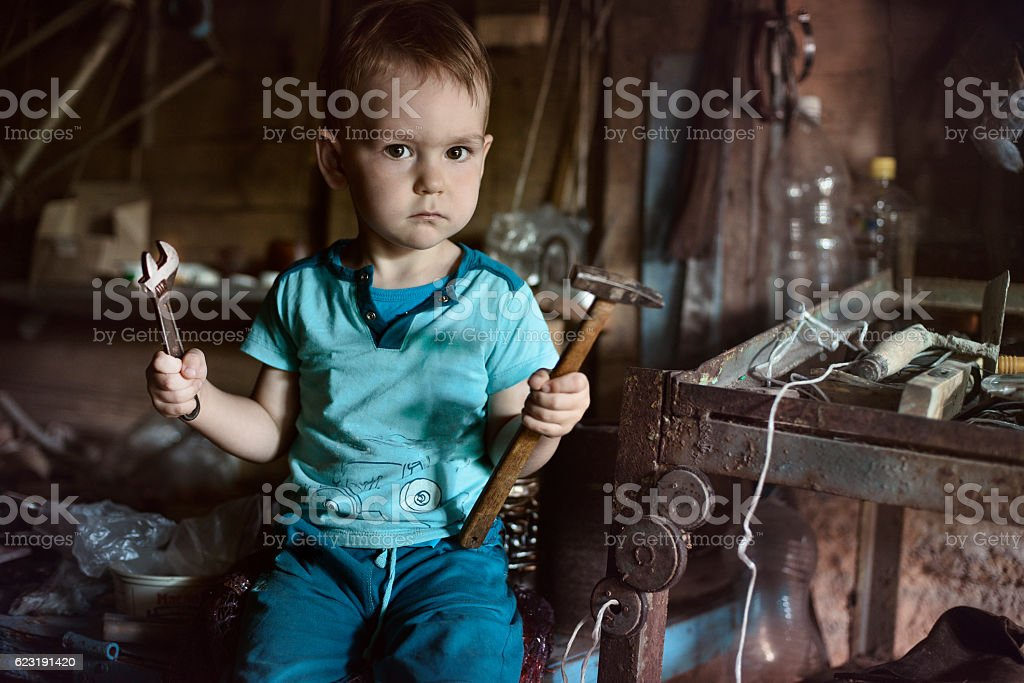 serious kid in the garage, holding a tool. – Foto