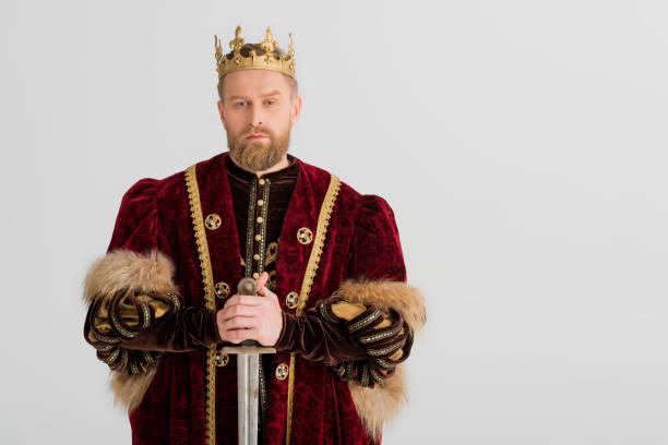 ernster könig mit krone halten schwert isoliert auf grau - könig stock-fotos und bilder