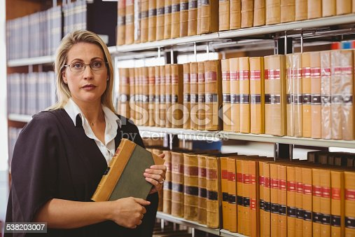 1070981872istockphoto Serious lawyer holding a book 538203007