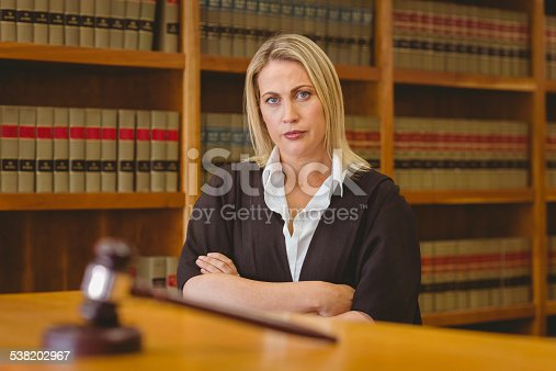 1070981872istockphoto Serious lawyer looking at camera with arms crossed 538202967
