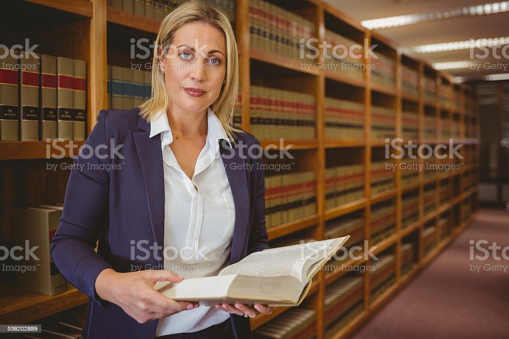 Serious librarian reading a book stock photo
