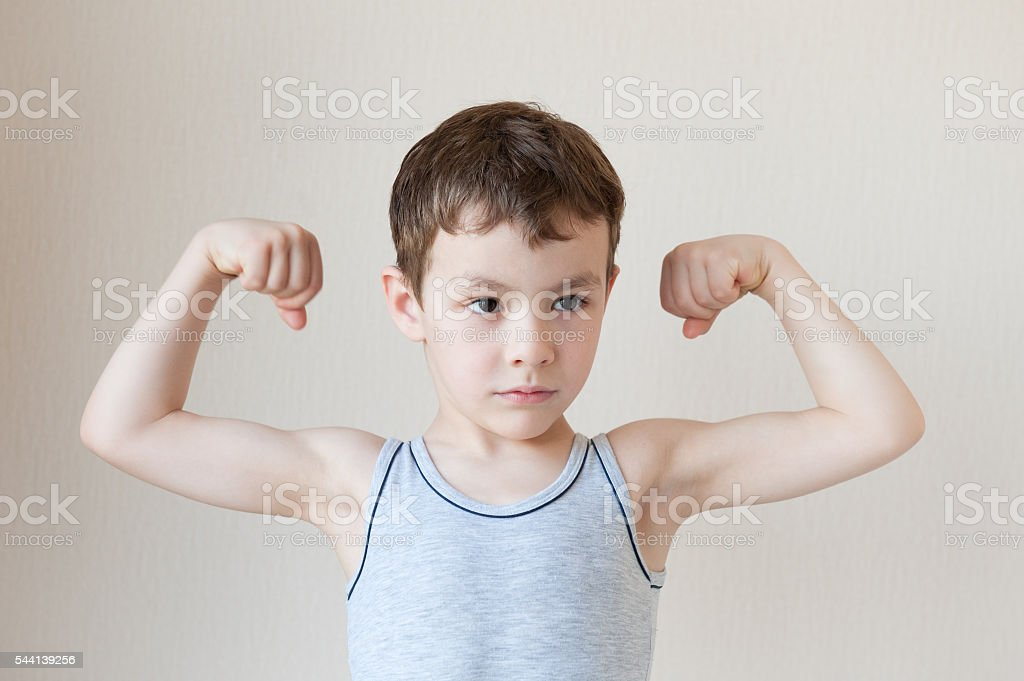 serious little boy in t-shirt showing muscles – Foto