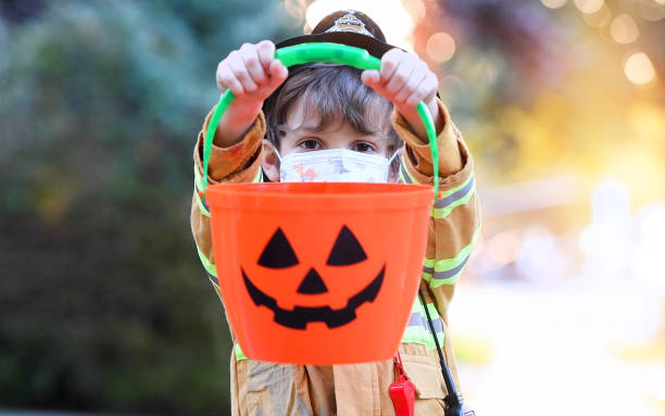Serious little boy wearing a halloween fireman costume and a protective face mask looking at the camera holding a Jack o Lantern bucket Serious little boy wearing a halloween fireman costume and a protective face mask looking at the camera holding a Jack o Lantern bucket halloween covid stock pictures, royalty-free photos & images