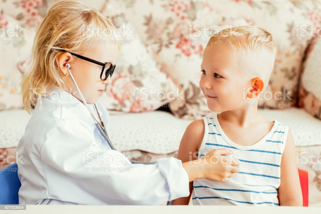 Serious little doctor examining boy patient stock photo
