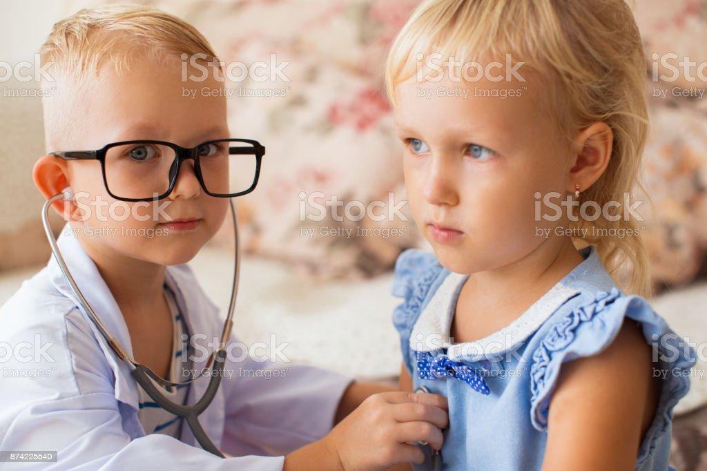 Serious little doctor examining girl in preschool stock photo