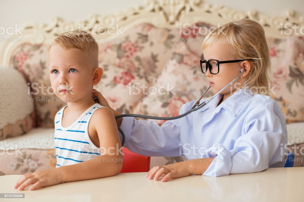 Serious little female doctor listening to patient stock photo