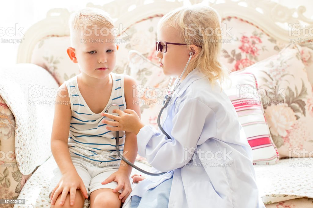 Serious little girl playing doctor with brother stock photo