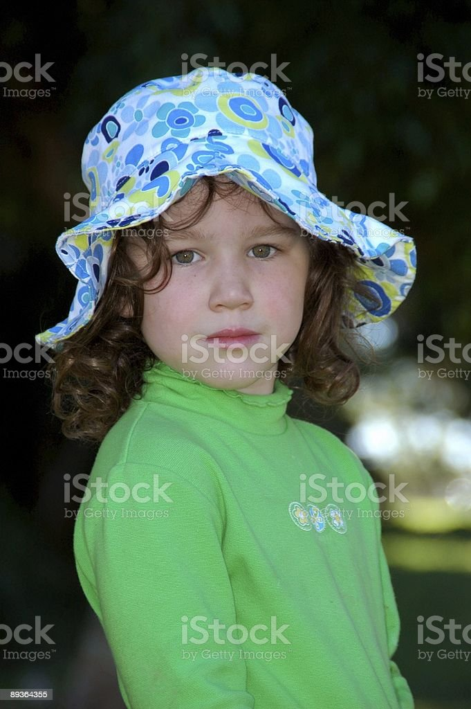 Serious little girl wearing large sun hat royalty-free stock photo