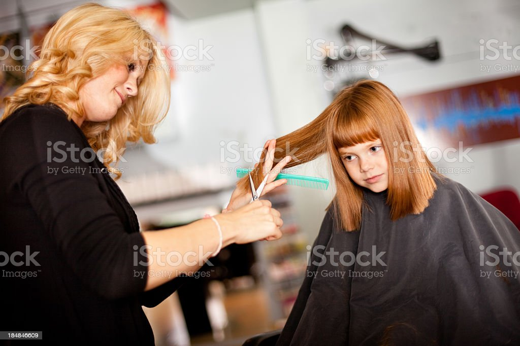 Serious Little Redhaired Girl Getting Haircut In Salon Stock Photo