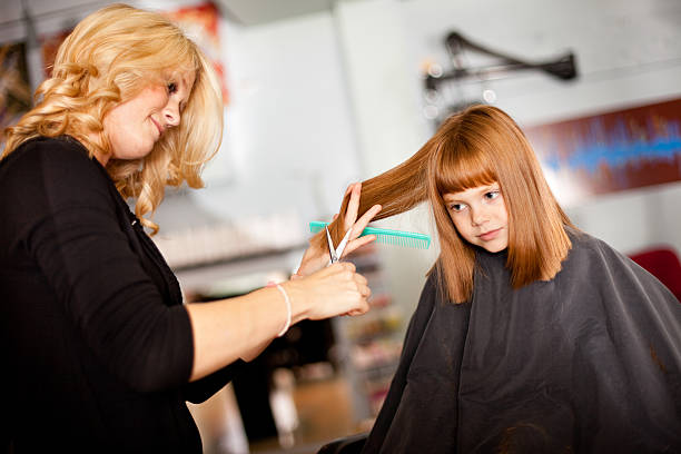 Serious Little Red-Haired Girl Getting Haircut in Salon stock photo