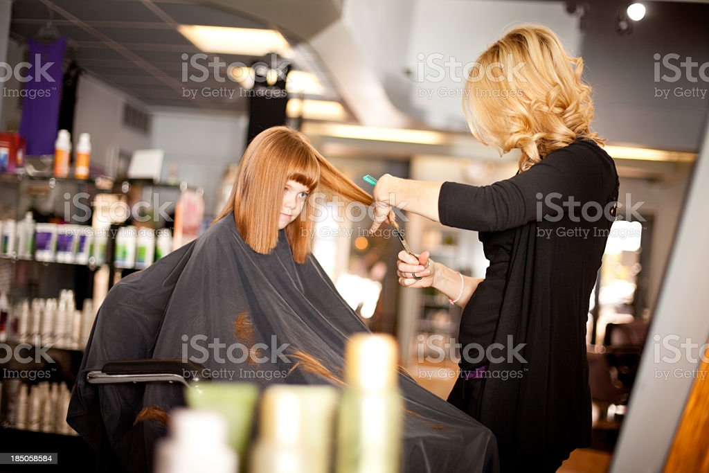 Serious Little Red-Haired Girl Getting Haircut in Salon royalty-free stock photo