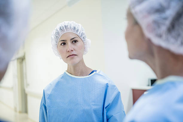 serious looking female surgeon wearing surgical cap - australian nurses stock photos and pictures