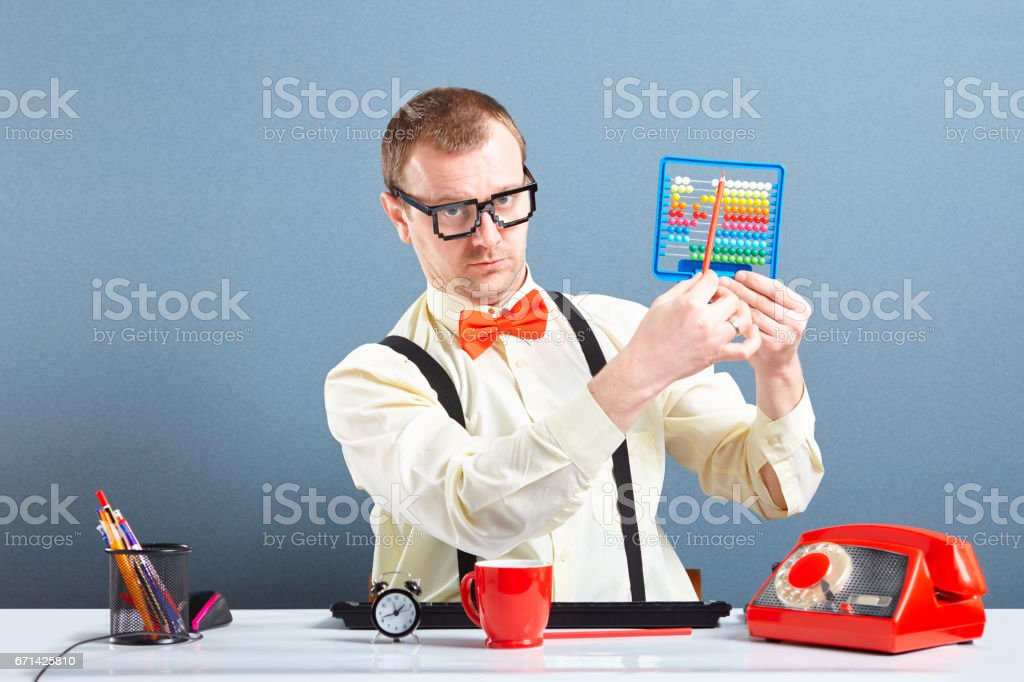 Serious looking nerd guy using abacus stock photo