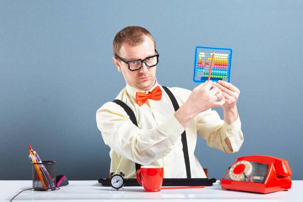 Serious looking nerd guy using abacus - foto stock