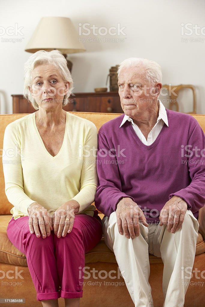 Serious Looking Senior Couple Sitting On Sofa At Home stock photo
