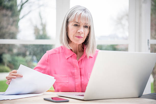 serious looking senior woman with laptop and paperwork - adults only stock photos and pictures