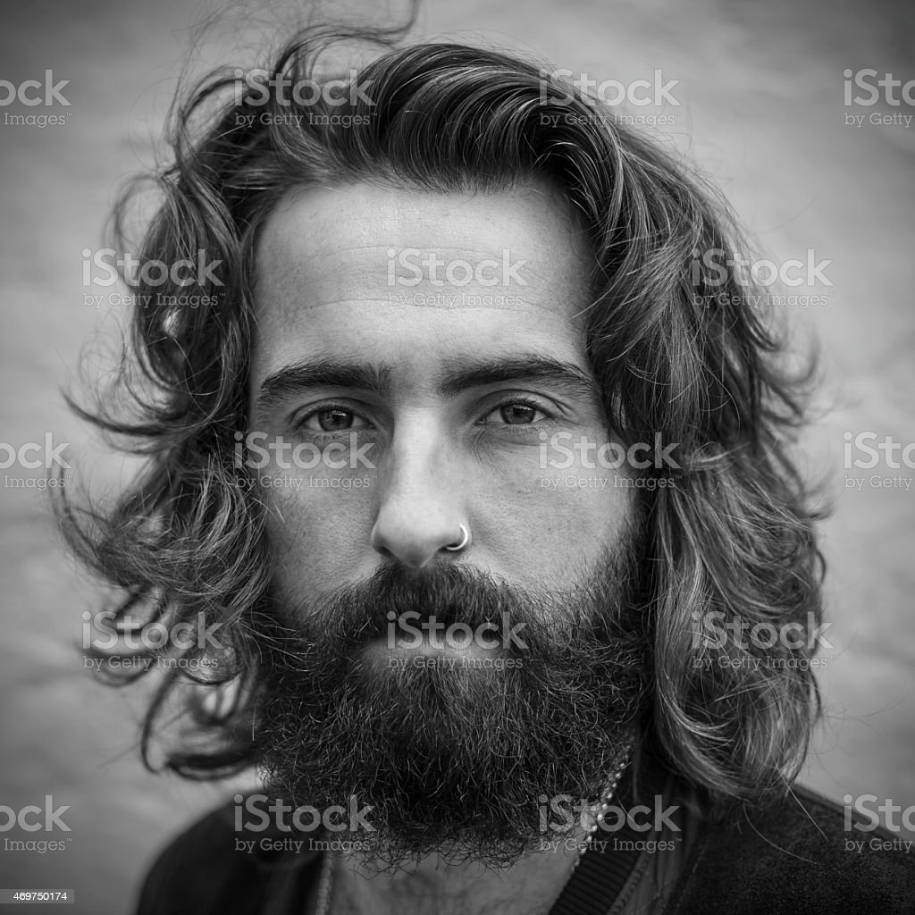 Serious looking young man with beard black & white portrait stock photo