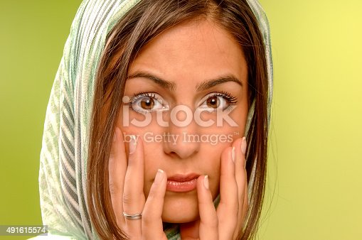 Close-up portrait of surprised beautiful Arabic girl holding her head in amazement, wearing a veil, looking at the camera