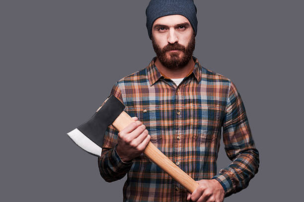 Serious lumberjack. Confident young bearded man holding a big axe and looking at camera while standing against grey background lumberjack stock pictures, royalty-free photos & images