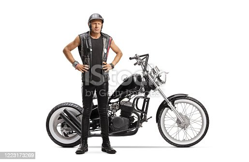 Full length portrait of a serious male biker with a helmet standing next to his chopper motorbike isolated on white background