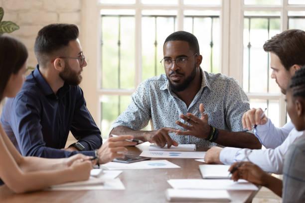 Seriöse männliche schwarze Führungskraft sprechen mit Mitarbeitern bei Briefing – Foto