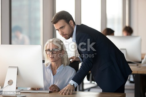 926404274 istock photo Serious male mentor supervising female employee helping with computer problem 1128967649