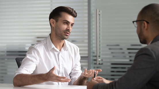 istock Serious male professional salesman consult customer at business meeting 1185095701