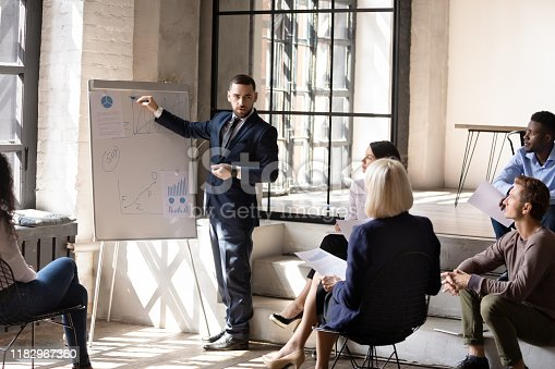 1031235468 istock photo Serious male speaker give business presentation drawing on flip chart 1182967360