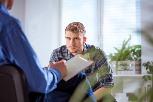 Serious Male Student Discussing With Therapist Stock Photo - Download Image Now