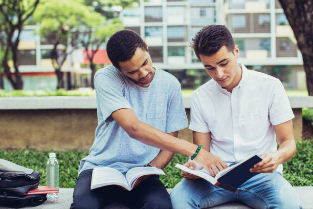 Serious male students doing homework together Portrait of young multiethnic student friends sitting together and doing homework in park. African American man pointing at workbook of friend workbook stock pictures, royalty-free photos & images