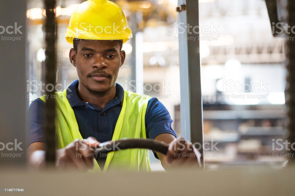 Serious male worker driving forklift in factory Serious male worker driving forklift. Engineer is wearing hardhat and reflective clothing. He is working in manufacturing industry. 25-29 Years Stock Photo