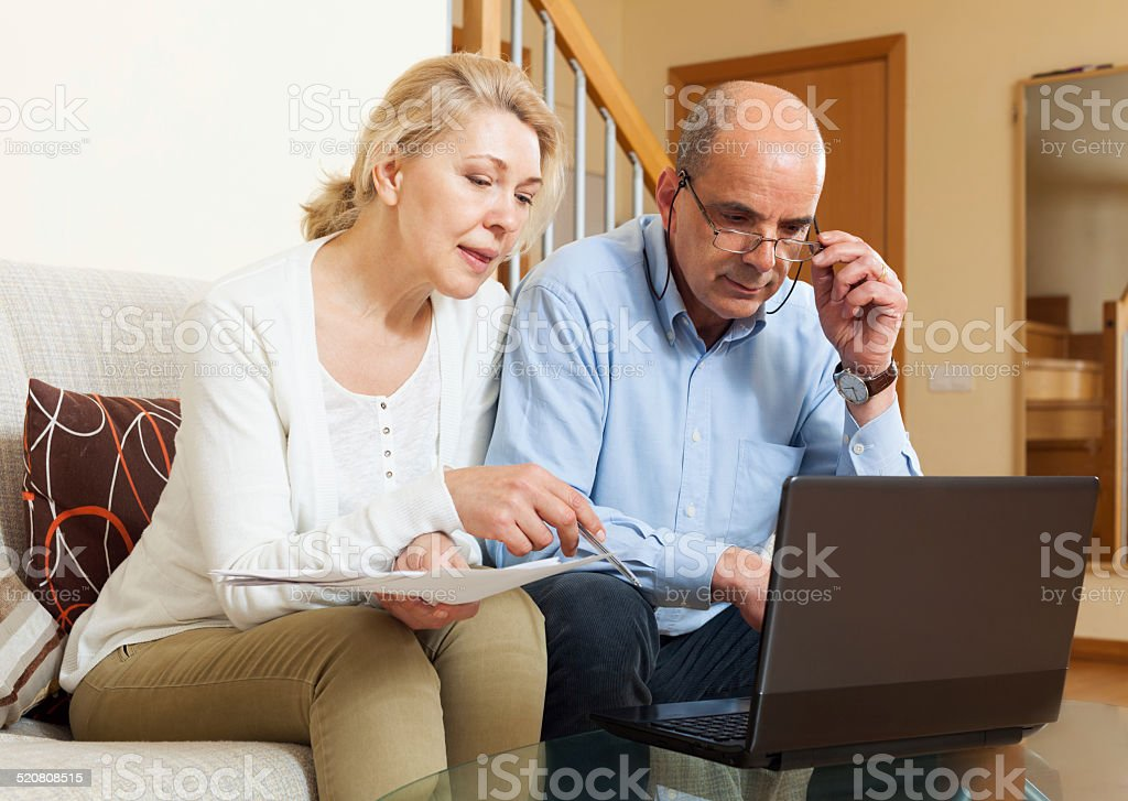 Serious man adn woman reading finance documents together Serious man adn woman reading finance documents together and using laptop in home interior 60-64 Years Stock Photo