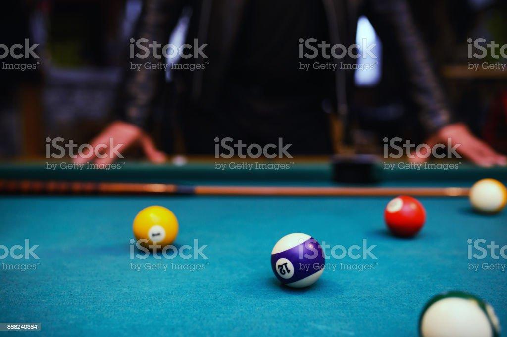 Serious man aiming at pool ball during billiard game