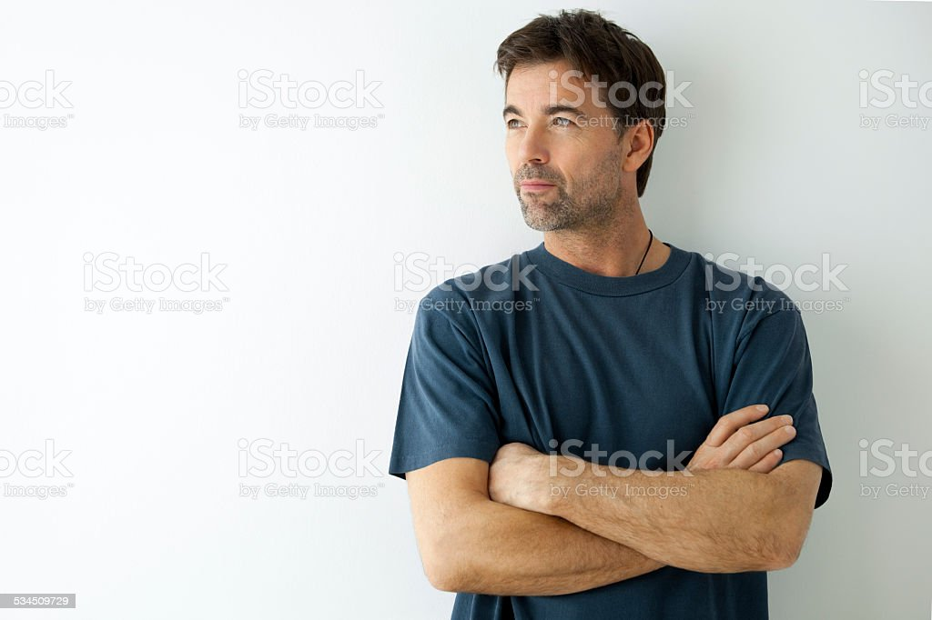 Serious Man Arms Crossed Looking Away stock photo
